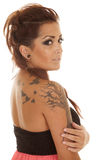 Woman tattoos pink side looking. A woman with a pink dress and tattoos on her is looking serious stock images