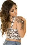 Woman with tattoos in a tank back. A woman in a tank showing off her tattoos, looking over her shoulder stock image