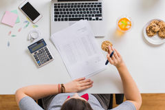 Woman with tax report eating cookie at office. Business, accounting and freelance concept - woman with calculator, papers and laptop computer eating cookie at royalty free stock photos