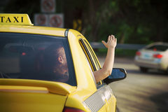 Woman in taxi waving hand out of car window Royalty Free Stock Image