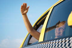 Woman in taxi waving hand out of car window Royalty Free Stock Photography