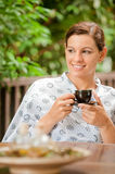 Woman with Tea. An attractive caucasian woman having a cup of tea in a robe outdoors stock photography