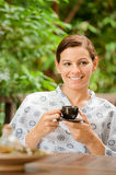 Woman with Tea. An attractive caucasian woman having a cup of tea in a robe outdoors royalty free stock photo
