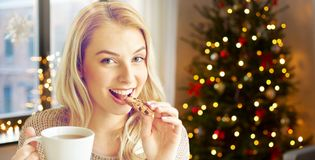 Woman with tea eating cookie on christmas at home stock photo