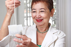Woman With Tea. Happy elderly woman inspecting some tea bags royalty free stock photography