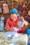 Woman with tea in Kyrgyzstan. Ala Archa, Kyrgyzstan - circa September 2011: Smiling native woman dressed in red t-shirt and with headcloth on her head pours tea Stock Photography