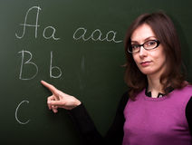 Woman teacher abc chalk board. Education scene: portrait of an attractive beautiful pretty cute young brown haired caucasian woman (lady, girl, female, person royalty free stock photos