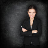 Woman teacher or business woman at blackboard. Holding chalk standing in suit by blackboard teaching or giving lecture. Young female professional portrait stock photo