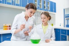 Woman teacher and girl student scientists pouring dust into tube with liquid Royalty Free Stock Photos