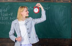 Woman teacher hold alarm clock. She cares about discipline. Time to study. Welcome teacher school year. Looking. Committed teacher complement qualified royalty free stock photos