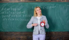 Woman teacher hold alarm clock. She cares about discipline. Time to study. Welcome teacher school year. Looking. Committed teacher complement qualified stock photos
