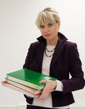Woman Teacher Holding Books. Woman teacher or instructor in a college, university, high school, middle school, elementary classroom holding a small stack of Stock Image