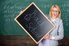 Woman teacher holds blackboard inscription back to school. Hiring teachers for new school year. Looking committed