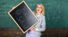 Woman teacher holds blackboard inscription back to school. Looking committed teacher complement qualified workforce