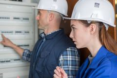 Woman and teacher measuring electrical current fuse board Royalty Free Stock Photos