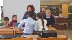 Woman teacher with primary school students. Teacher talking to schoolchildren. Chapaevsk, Samara region, Russia - May 10, 2019: Elementary school of the city of stock video