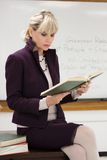 Woman Teacher Reading. Woman teacher or instructor in a college, university, high school, middle school, elementary classroom sitting on her desk holding a book Stock Photos