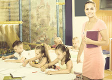 Woman teacher standing with textbook in school class. Young attractive women teacher standing with textbook in school class with kids. Focus on the woman Royalty Free Stock Image