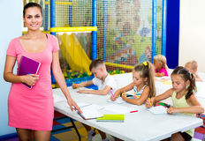 Woman teacher standing with textbook in school class Stock Photo