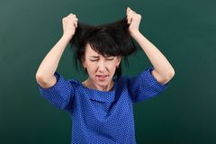 Woman teacher in stress posing by chalk Board, tears her hair, learning concept, green background, Studio shot Stock Photos