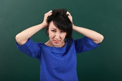 Woman teacher in stress posing by chalk Board, tears her hair, learning concept, green background, Studio shot Royalty Free Stock Images