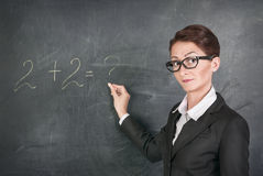 Woman teacher teaching maths. Woman teacher in glasses teaching maths Royalty Free Stock Images