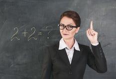 Woman teacher teaching maths. Woman teacher in glasses teaching maths and showing finger Stock Image