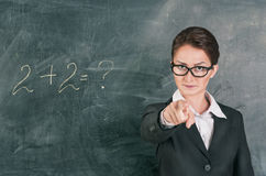 Woman teacher teaching maths and pointing on someone. Woman teacher in glasses teaching maths and pointing on someone Royalty Free Stock Photos