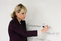 Woman Teacher Writing On Board. Woman teacher or instructor in a college, university, high school, middle school, elementary classroom writing on a white board Royalty Free Stock Image