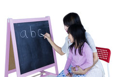 Woman teaches alphabet to her daughter. Young women teaching alphabet to her daughter while writing letter with a chalk on blackboard stock photo