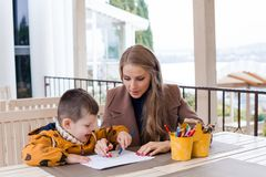 Woman teaches the boy to draw with colored pencils. 1 Royalty Free Stock Image