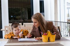 Woman teaches the boy to draw with colored pencils. 1 Stock Photos