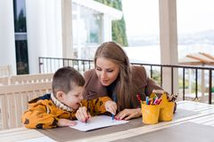 Woman teaches the boy to draw with colored pencils. 1 Royalty Free Stock Photos