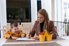 Woman teaches the boy to draw with colored pencils. 1 Royalty Free Stock Photography