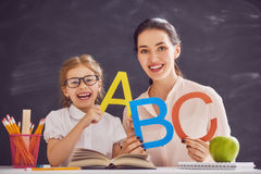 Woman teaches child the alphabet. Back to school! Child is learning to write. Adult women teaches child the alphabet stock image