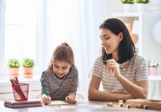 Woman teaches child the alphabet Royalty Free Stock Photos