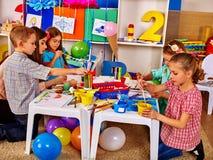 Woman teaches children to handicrafts made of paper in kindergarten . Stock Photography