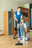 Woman teaches  girl to use the vacuum cleaner Stock Photos