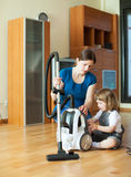 Woman teaches  girl to use the vacuum cleaner Stock Image