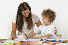 Woman teaches her child how to draw. She has her arm around him. They're sitting at a table. Both are smiling stock photo
