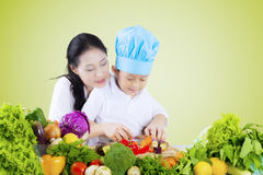 Woman teaches her child to cut vegetables Stock Photo