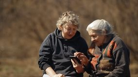 A woman teaches her old mother to use a smartphone. Portrait of two women looking at smartphone pictures. stock footage