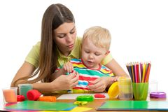 Woman teaches kid boy handcraft at kindergarten or playschool royalty free stock image