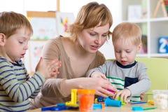 Woman teaches kids handcraft at kindergarten or playschool. Woman teaches children handcraft at kindergarten or playschool royalty free stock image