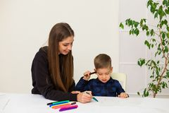 Woman teaches a young boy paint markers. Woman teaches a young boy to draw flamasterami stock photography