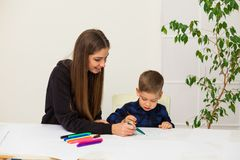 Woman teaches a young boy paint markers. Woman teaches a young boy to draw flamasterami royalty free stock photo