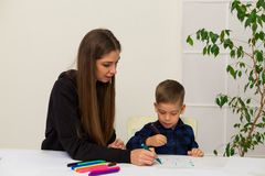 Woman teaches a young boy paint markers. Woman teaches a young boy to draw flamasterami stock image