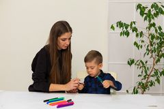 Woman teaches a young boy paint markers. Woman teaches a young boy to draw flamasterami royalty free stock photography