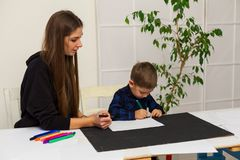 Woman teaches a young boy paint markers. Woman teaches a young boy to draw flamasterami royalty free stock photos