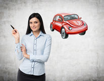 A woman is teaching a basis of road traffic regulations. A sketch of a red car is drawn on the concrete wall. Royalty Free Stock Photography